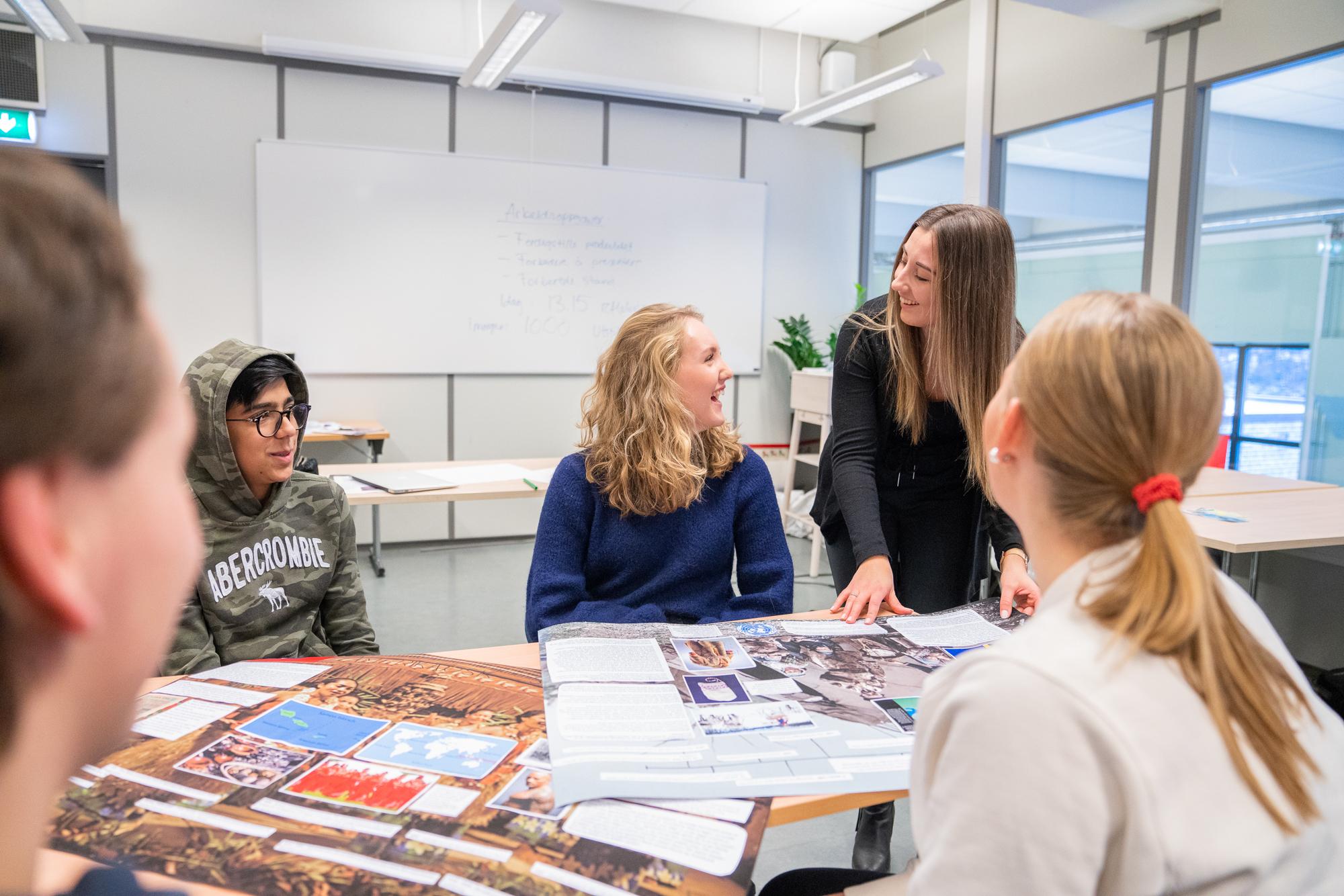 Fire elever arbeider rundt et bord men lærer forklarer. Foto.