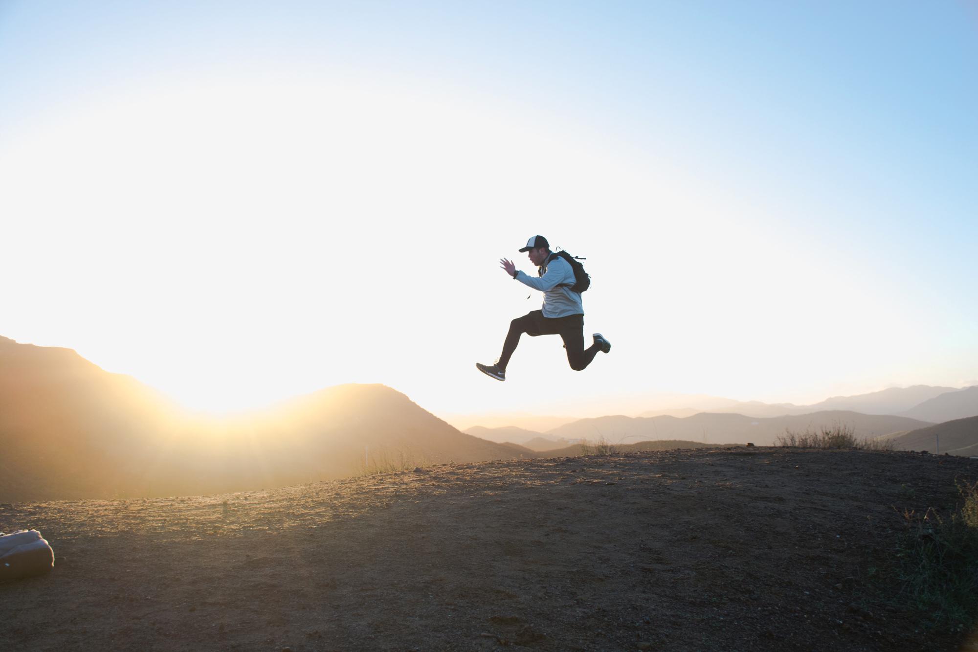 Gutt som hopper på et fjell. Foto.