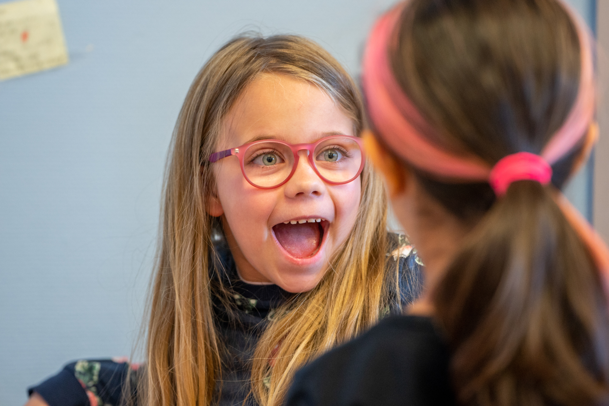 Glad jente med rosa briller. Foto.