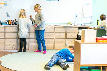 Montessorimiljø på Heltberg barne- og ungdomsskole. Elever jobber ved lav benk og på stort teppe på gulvet. Foto.