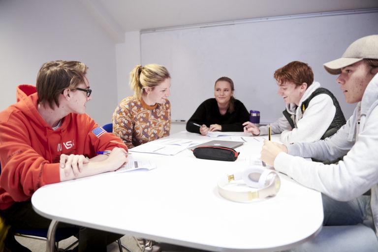 Elever og lærer arbeider samme rundt et bord. Foto.