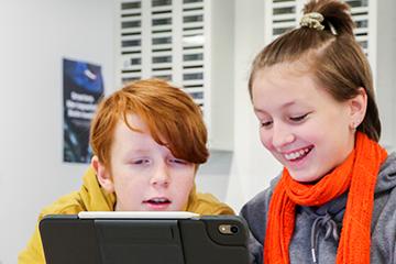 To elever i ulike alder jobber sammen på iPad. Foto.