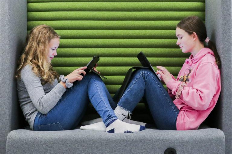 To elever jobber på iPad i sofa. Foto.
