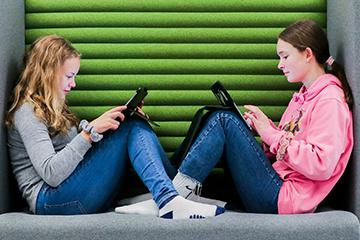 To elever som jobber på iPad i sofa. Foto.