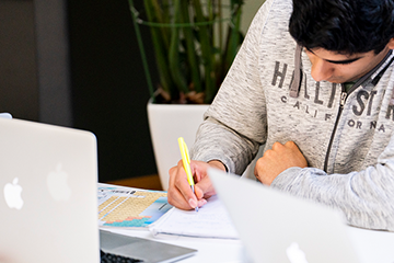 Elev som jobber med Mac, penn og papir. Foto.
