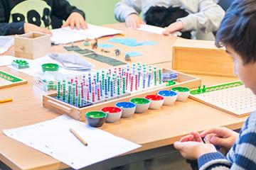 Montessorimaterill. Regansrør med fargede kuler. Foto.