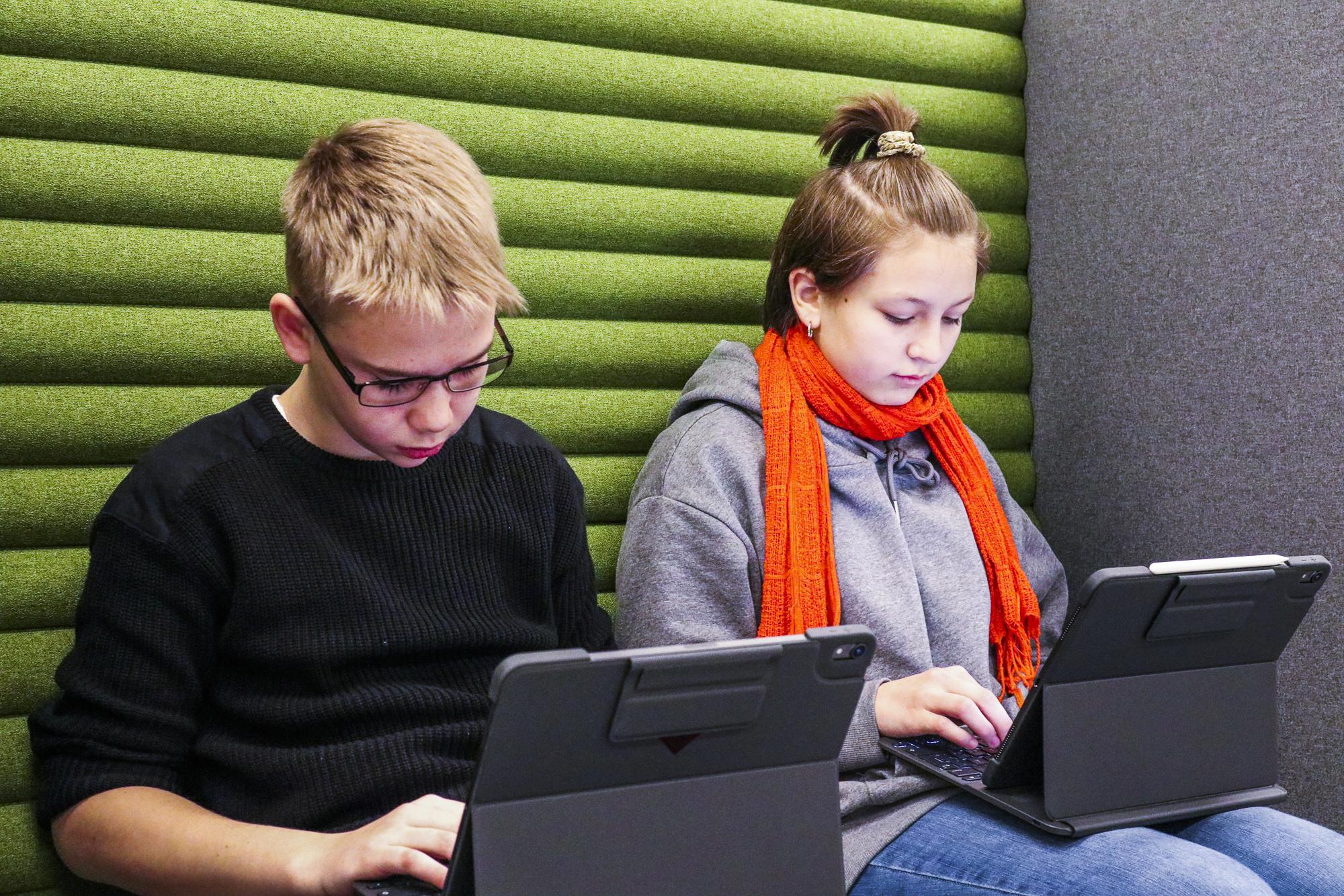 To elever som arbeider på iPad. Foto.
