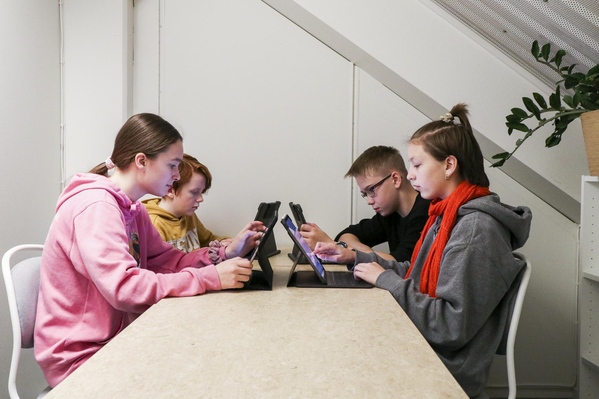 Elever som jobber på iPad rundt et bord. Foto.